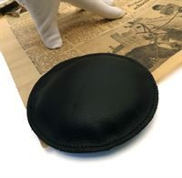 Circular leather paperweight